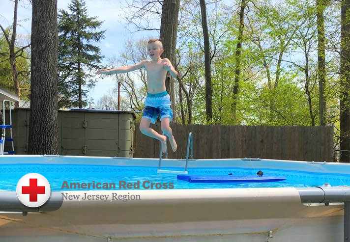 Brandon jumping in pool with logo